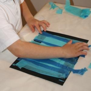 Gluing tissue paper onto back of frame