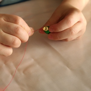 Threading cotton onto tiny baubles