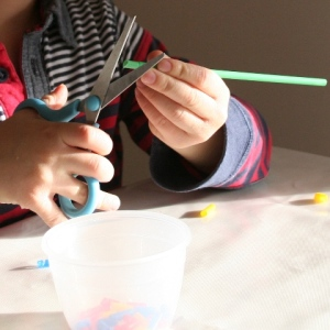 Cutting drinking straws to make beads