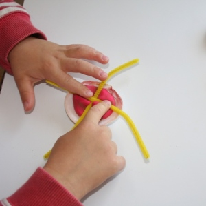 Pushing pipe cleaner legs into Plasticine